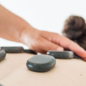 Hot Stone Massage mit Hand der Therapeutin