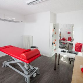 Massageliege in rot in einem Therapiezimmer